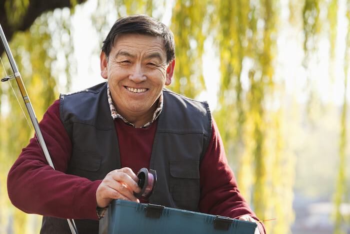 Older smiling man with fishing pole