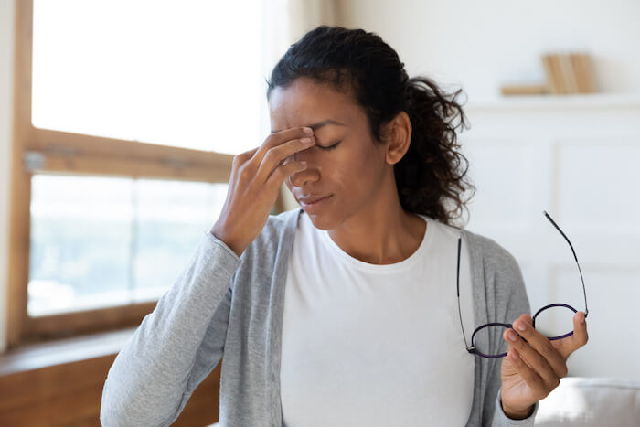 Woman rubbing eyes after removing glasses
