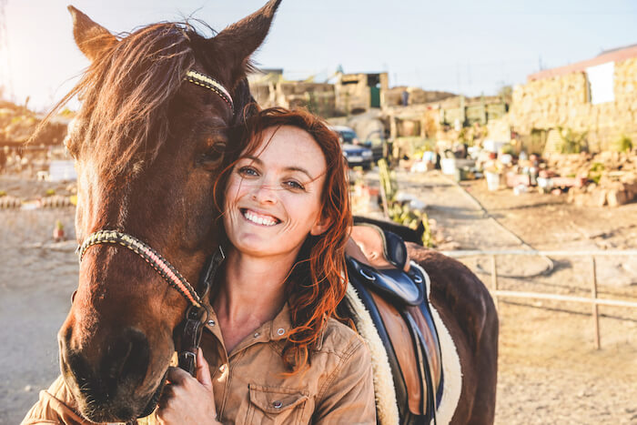 Woman holding reigns to horse