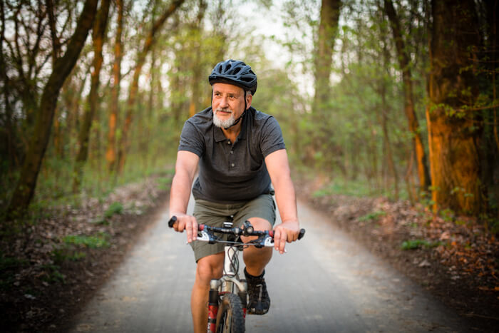 Senior man on bike in forest