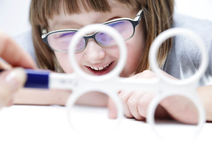 Little girl in glasses looking at vision therapy tool